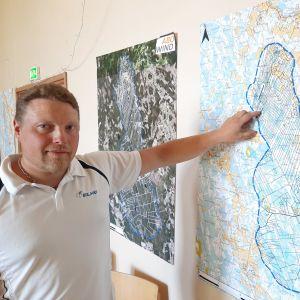 en man står framför en karta av purmo
