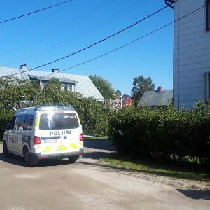 En polisbil står på gatan utanför ett vitt hus men grön häck runt. Bredvid bilen syns polisens avspärrningsband.