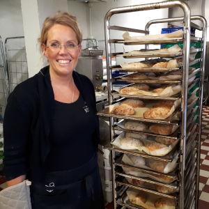 Kvinna bredvid en ställning med nybakade bröd.