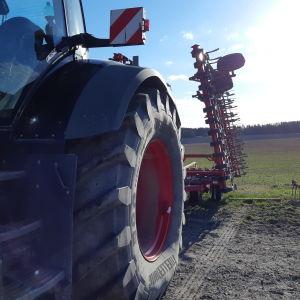 En traktor och en harv vid en åker.