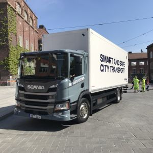 """Vit lastbil med texten """"smart and safe citytransport"""" på sidan."""