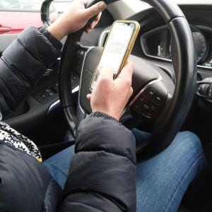 Person läser något på telefonen samtidigt som hen kör bil.