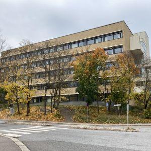 En gultegels skolbyggnad i fyra våningar med höstgula träd omkring.