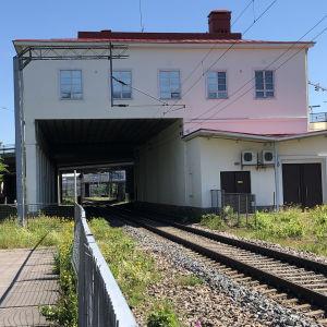 Vanha valkoinen asemarakennus, jossa punainen peltikatto. Rautatiekiskot kulkevat talon läpi.