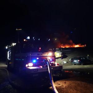 Brandbil framför ett brinnande berg av bildäck vid Jakobstads gamla avstjälpningsplats.