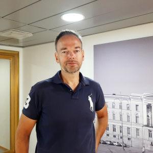 En man i en blå pikétröja. Gråspräckligt skägg och ljusbrunt hår. Står framför en vägg med en tavla och en dörr som har guldfärgad karm.