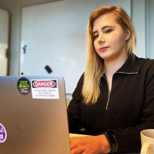 Laura Kankaala skriver på sin gråa dator iklädd en svart tröja.