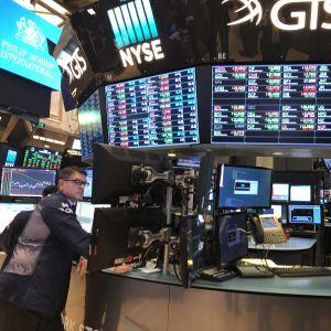 En aktiemäklare följer kurserna på sin skärm bland många mäklare och skärmar vid runda deskar.