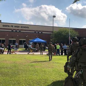 Poliser och sjukvårdspersonal och representanter för medierna utanför Santa Fe High School efter massakern där.