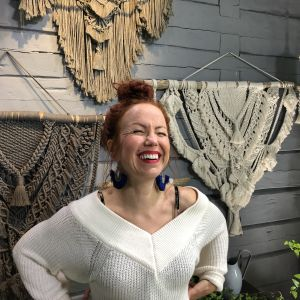 Naurava nainen makrameetöiden edessä
