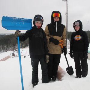 Tre unga står i skidbacke.