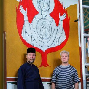 Piispa Arseni ja Jyrki Pouta maalaamansa seinämaalauksen edessä. Maalauksessa palava pensas.