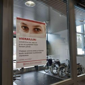 Koronavierailuja koskeva juliste sairaalan ovessa.