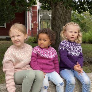 Tre flickor iklädda handstickade strömsöbarntröjor sitter på en bänk.