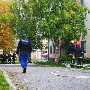 Två brandmän står och talar med varandra intill en tegelbyggnad. Till vänster i bilden går en polisman på en grusväg.