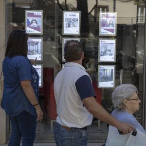 En medelålderspar och en äldre dam i rullstol tittar på ett skyltfönster med bostadsannonser i Lissabon.