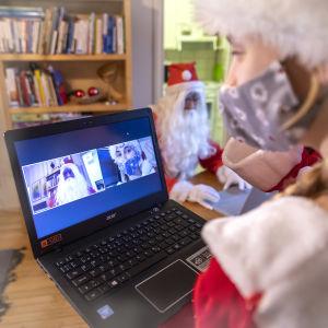 Tonttutyttö katsoo tietokoneelta etäyhteydellä joulupukkia.