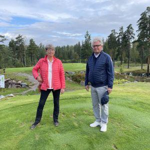 Porträtt av Annika Colérus och Henrik Sarajas som står bredvid varandra och ser in i kameran. De står på en golfbana, i bakgrudnen finns terränghinder.