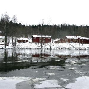 En isig å och hus vid kanten av ån.