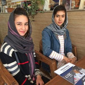 Kvinnorna Shaqaiq och Arzoo ler mot kameran på ett kafé i Kabul.