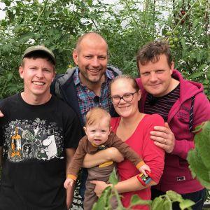 John Silander, Matias Jungar, lilla Sidonia Silander, Runa-Linn Silander och Michael Björklund står i ett växthus där det odlas tomater.