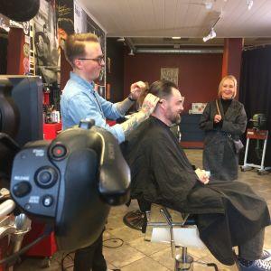 Parturi leikkaa Tuhkimotarinoiden Timon hiuksia. Stylisti Outi Broux seuraa taustalla.