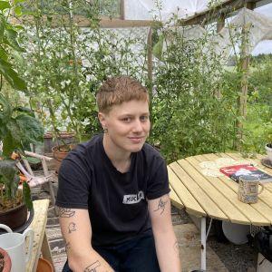 """Edith Hammar sitter i sitt växthus och tittar in i kameran. I bakfgrunden skymtar växter och gröna kvistar, och boken """"Homo Line"""" på bordet."""