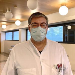 Asko Järvinen med ett munskydd tittar rakt in i kameran.