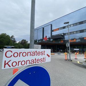 En skylt till corona provtagning. I bakgrunden ses en sjukhusbyggnad.