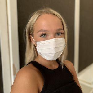 Ung blond kvinna med munskydd väntar på sin tur till drop-in mottagning för coronavaccinering i Malax..