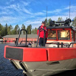 Mies seisoo Konneveden järvipelastajien pelastusaluksen kannella.
