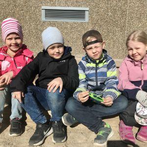 Fyra barn sitter på en sandlådskant och kisar mot solen.