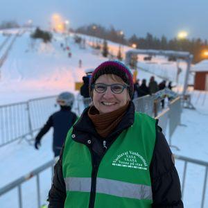 Leende kvinna utomhus. I bakgrunden köar slalomåkare till skidlift. Kvinnan är klädd i grön väst där det står Vasa - vuxna på stan.