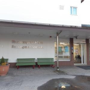 En bild på Raseborgs sjukhus byggnads entre. På väggen står raseborgs sjukhus med silvriga bokstäver