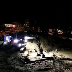 En grävmaskin med stark ledbelysning jobbar i mörkret i ett centrumområde, sand och grus syns och man kan se ljus från skyltfönster.