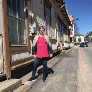 Thérèse Meriheinä står utanför ett gammalt beige hus i Lovisa medan solen skiner.