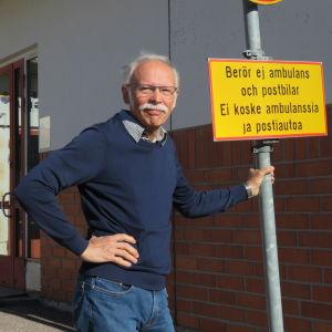"""En man med grått hår, mustasch och blå tröja står utanför Ingå hälsocentrals ingång. Han står och håller i en trafikskylt som förbjuder trafik, men med tillägget """"berör ej ambulans och postbil""""."""
