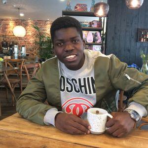 Serge Atakayi sitter på café i Jakobstad, juni 2017.