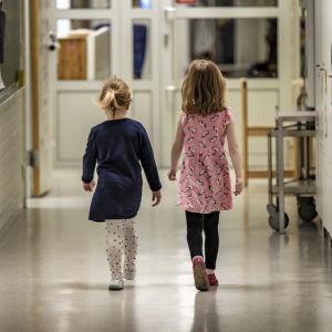 Kaksi tyttölasta kävelee käytävällä