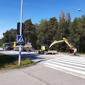 Kaivinkone työstää liikenteenjakajassa paikkaa valopylväälle.