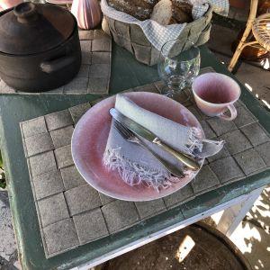 Pöytä on katettu. Pöydällä on pellavahuvasta tehdyt pannunalusta, leipäkori ja tabletin.