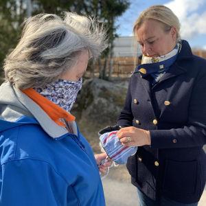 Två kvinnor står utomhus, den ena håller i munskydd av tyg.