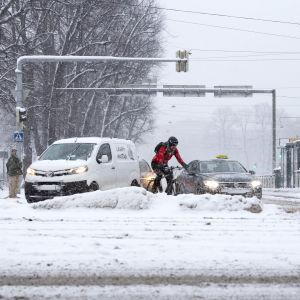 Autoilijoita ja pyöräilijä lumen keskellä Mannerheimintiellä.