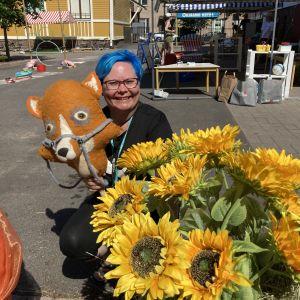 Sinihiuksinen Jenni Kuusitie pitää kädessään keppikettu-nukkea ja hymyilee. Kuvassa myös auringonkukkia.