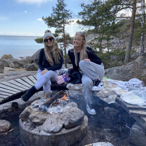 Pinja och Riina sitter och ler vid en öppen eld med havet i bakgrunden.