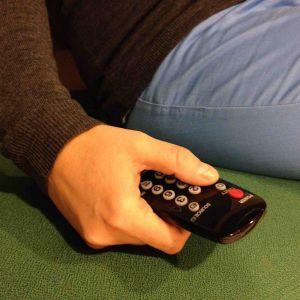 hand som håller i fjärrkontroll