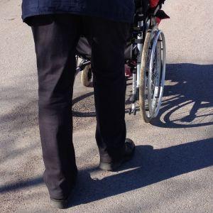 Person skuffar en person i rullstol.