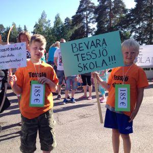 Två pojkar från Tessjö skola håller i skyltar.