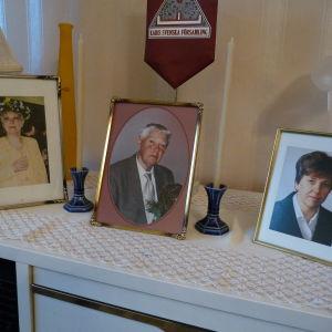 På ett bord hemma hos Gurli Nurmi finns fotografier på hennes avlidna man och döttrarna som också gått bort