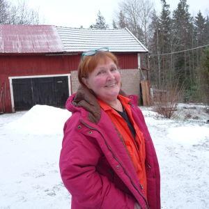 Marianne Tapper ute på på sin gård. Bakom syns ladugården